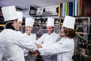 Team of chefs putting hands together and cheering