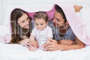 Couple enjoying with baby under blanket on bed