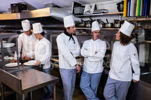 Team of chefs standing together in commercial kitchen