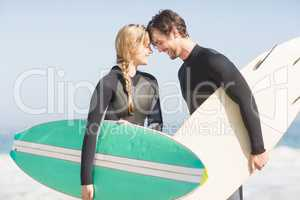 Happy couple standing head to head with surfboard