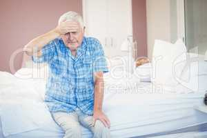 Suffering senior man holding his head st home