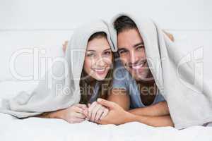 Portrait of happy couple lying under blanket