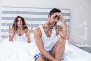 Man sitting while wife shouting at him