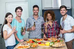 Happy multi-ethnic enjoying alcohol and pizza at table