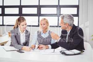 Business people discussing with client over documents