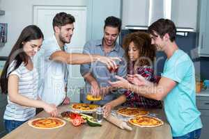 Multi-ethnic friends preparing pizza on kitchen table