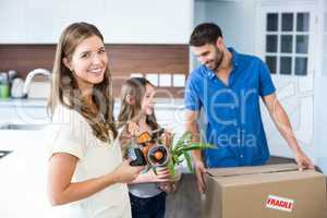 Portrait of woman helping family in packing