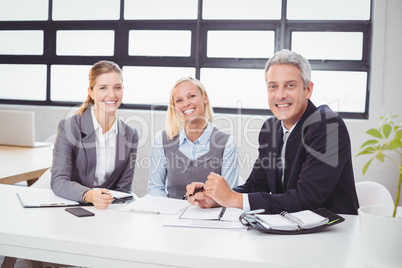 Happy business people sitting with client at desk