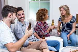 Multi-ethnic friends smiling while enjoying beer