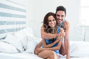 Portrait of cheerful young man embracing wife from behind on bed