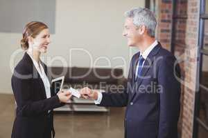 Businesswoman giving business card to client in office