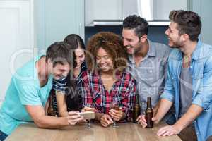 Multi-ethnic friends looking in mobile phone at home