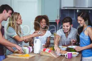 Happy friends standing at breakfast table