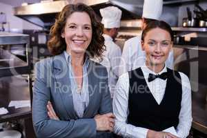 Restaurant manager and waitress smiling in commercial kitchen