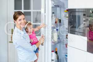 Woman opening refrigerator while carrying baby girl
