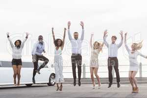 Well dressed people jumping next to a limousine