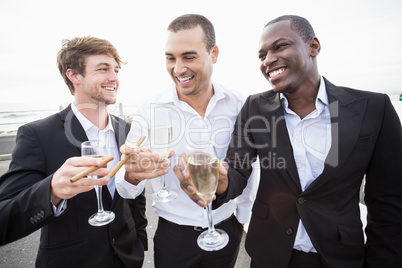Well dressed men drinking champagne next to a limousine
