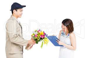 Delivery man taking signature of woman while delivering flowers