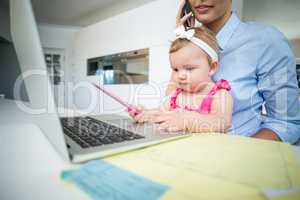 Playful baby girl sitting with mother by laptop
