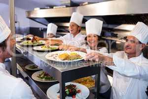 Chefs handing dinner plates through order station