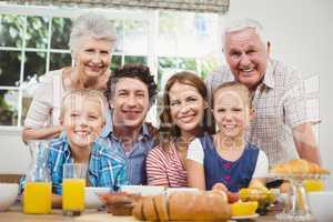 Happy multi-generation family by breakfast table