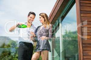 Happy couple drinking champagne at balcony in resort