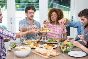 Multi-ethnic young friends having meal at table
