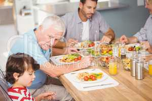 Grandfather assisting grandson while having breakfast