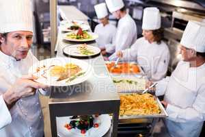 Chef handing dinner plates through order station