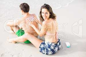 Woman applying sunscreen lotion on mans back