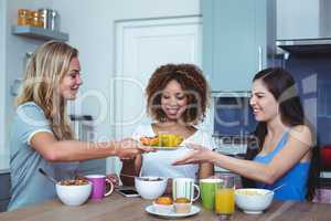 Multi ethnic friends holding plate with papaya in house