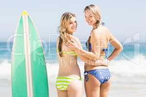 Two happy women standing next to a surfboard on the beach