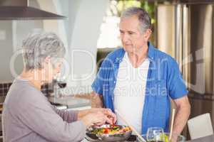 Active senior couple preparing salad