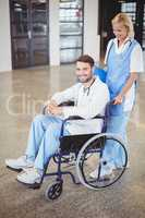 Portrait of smiling doctor sitting on wheelchair with female col