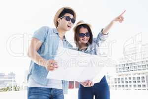 Happy young couple using map for direction