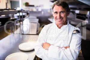 Smiling chef holding ladle in the kitchen