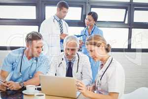 Medical team using laptop in conference room