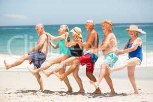 Seniors dancing in a row at the beach