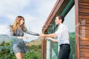 Happy young couple dancing at balcony in resort