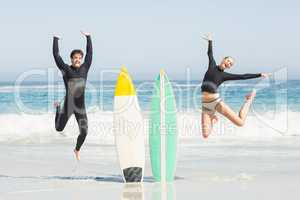 Excited couple jumping next to surfboards
