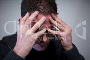 Depressionen und Burn-Out. Mann fasst sich mit Fingern an den Kopf.
