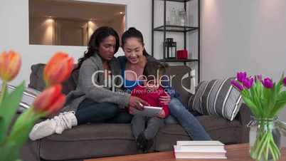 Lesbian Couple Using Ipad Tablet With Child Happy Homosexual Family
