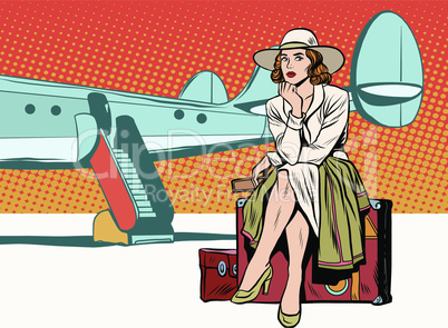 Tourist girl sitting on a suitcase, travelling by plane