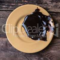 Melted dark chocolate on the yellow plate