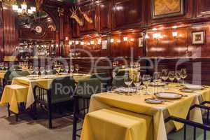 Tables laid for guests at wood-panelled restaurant