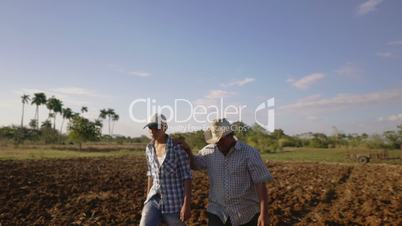 27-Farmer And Son Walking In Seeded Field Talking Planning Cultivations
