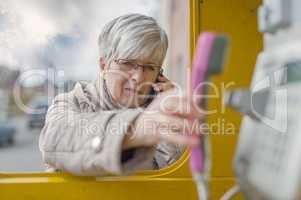 Seniorin mit Smartphone und Telefonhörer