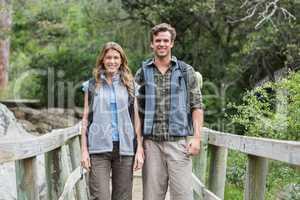 Portrait of smiling hikers on footbridge
