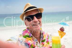 Happy senior man with a cocktail drink