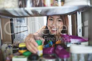 Portrait of young woman picking a bottle from storage cabinet